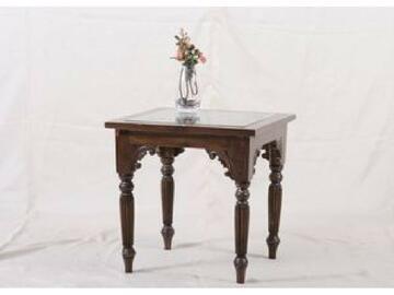 Tavolino in legno completamente scolpito e rifinito con un piano di appoggio in vetro. La parte superiore del tavolino e formata da una scultura in legno con motivo floreale che riprende gli attacchi delle gambe a cipolla anch'essi scolpiti.